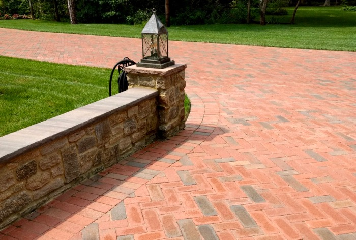 Stone wall complements full range red driveway.