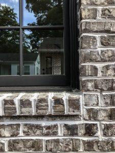 Tufts House brick dark trim in Tudor revival home